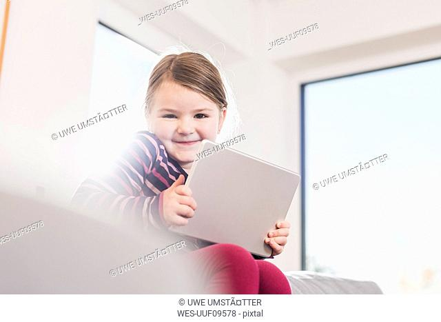 Little girl using digital tablet, sitting on couch