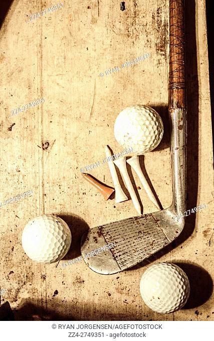 Old fashioned still life shot of a vintage golfing iron with ornate wooden handle coupled with a set of three golf balls and tees on shabby grunge background