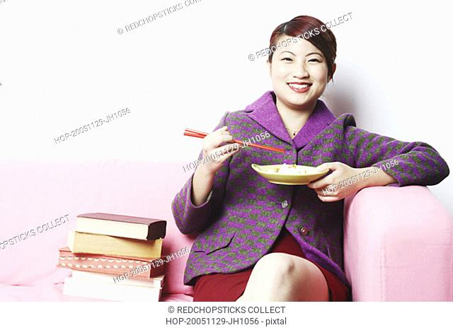 Portrait of a young woman eating with chopsticks