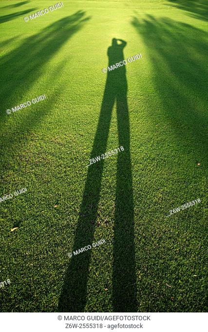 Photographing his own shadow in the late evening on a golf course