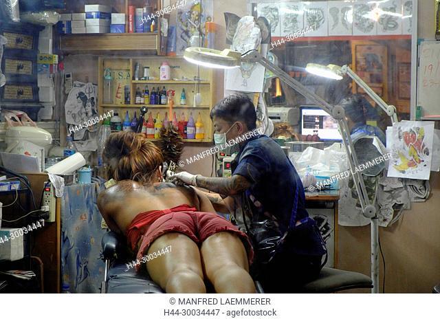Asien, Thailand, Chonburi, Pattaya, Frau bekommt Tattoo an der Schulter
