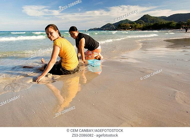Two Thai women sitting on the beach, Chaweng, Koh Samui, Surat Thani Province, Thailand