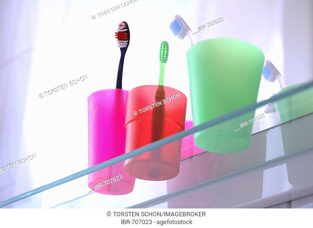 Three toothbrushes in colored toothbrush tumblers