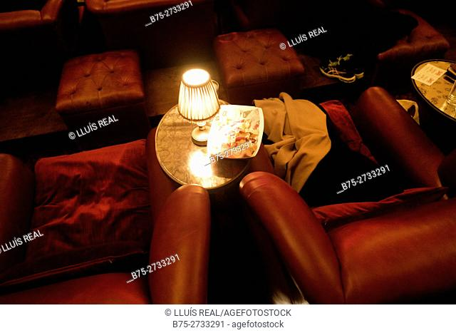 Close-up of two red armchairs, small table with a lit lamp and a tray with leftover food. Electric Cinema, Portobello Rd., London, England