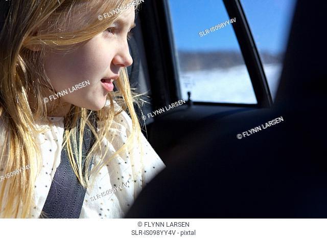 Young girl looking through car window