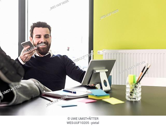 Businessman holding smart phone, talking