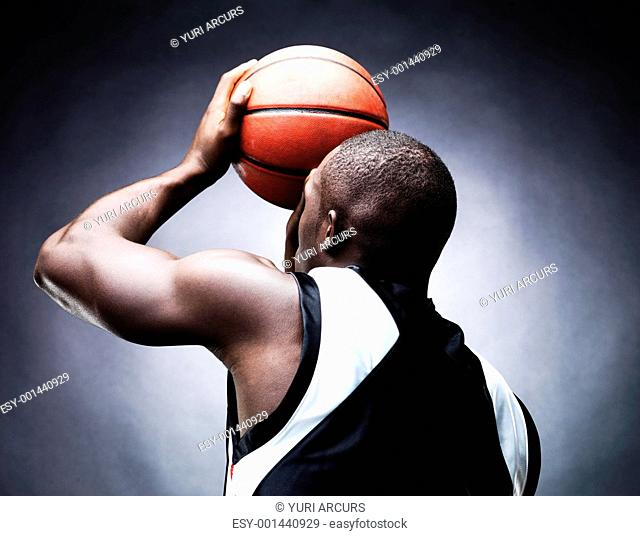 Rear view of a young male basketball player in free throw pose against grunge background