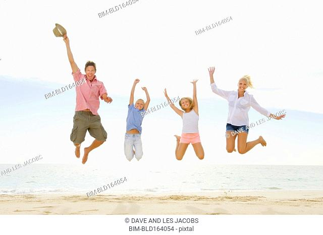 Caucasian family jumping for joy on beach
