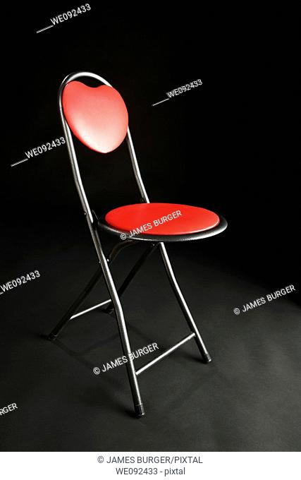 A red chair on a black studio background