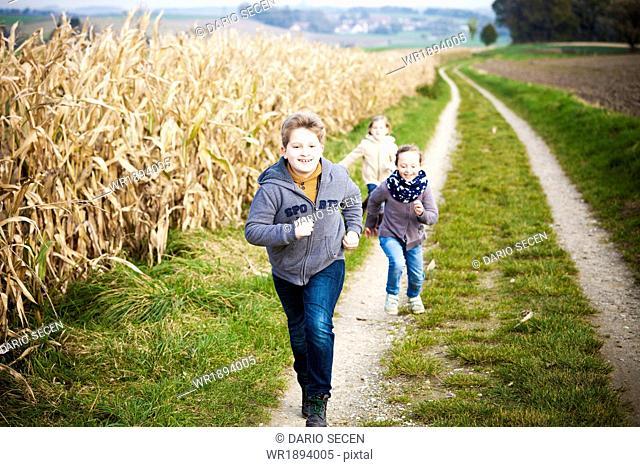 Three children running on path
