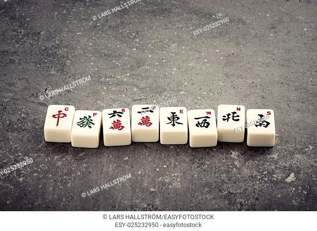 Mahjong board game pieces lying on stone table. Concept of asian or chinese leisure activity, recreation and traditional games
