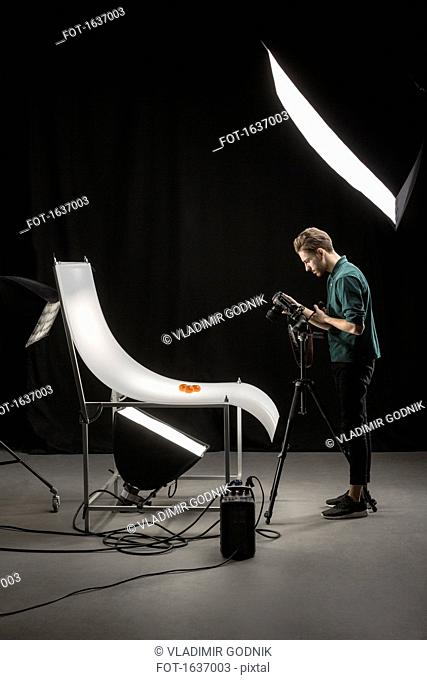 Side view of photographer photographing food on backdrop at studio