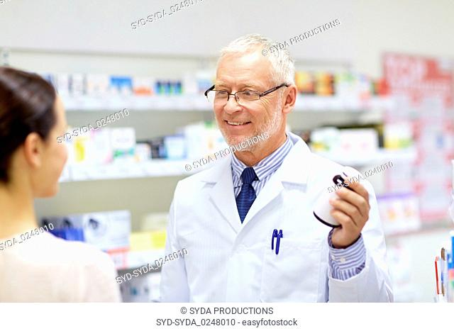 apothecary and woman with drug at pharmacy