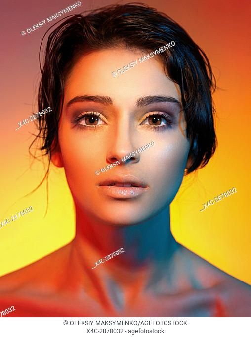 Artistic beauty portrait of a young woman beautiful face with short dark hair lit with colorful, red and yellow lights