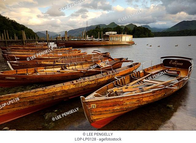 England, Cumbria, Keswick, Sunset over rowing boats beached at Derwentwater landing stage
