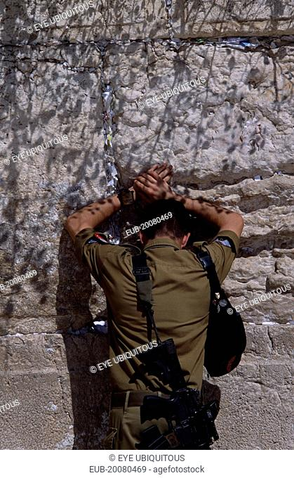 An Israeli Soldier in army uniform with a M16 Assault Riffle around his shoulder praying at The Western Wall