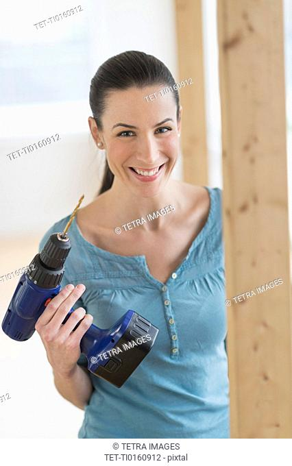 Portrait of woman using hand drill