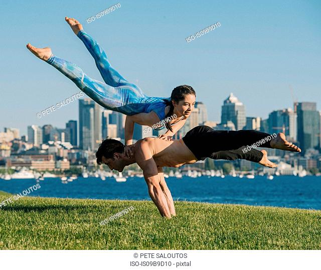 Teenage girl and young man, outdoors, man balancing on hands, girl balancing on hands on man's back