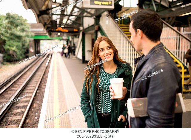 Couple on railway platform face to face smiling