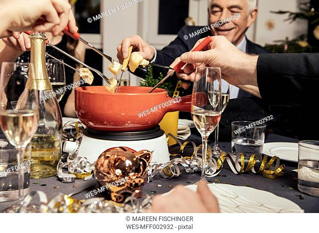 Friends eating cheese fondue on New Year's Eve