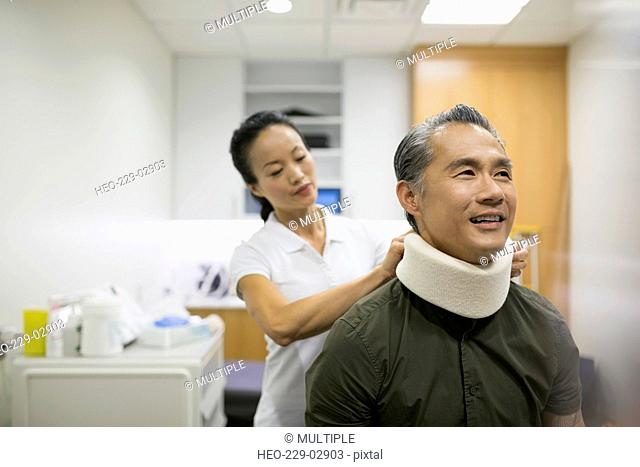 Physical therapist placing neck brace on patient