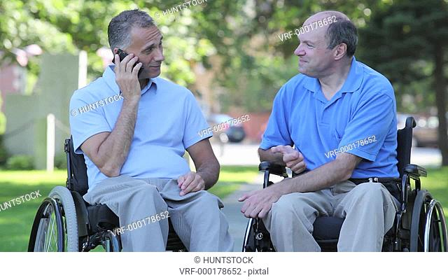 Two men in wheelchairs in park talking on a smartphone one with spinal cord injury and one with Friedreich's Ataxia