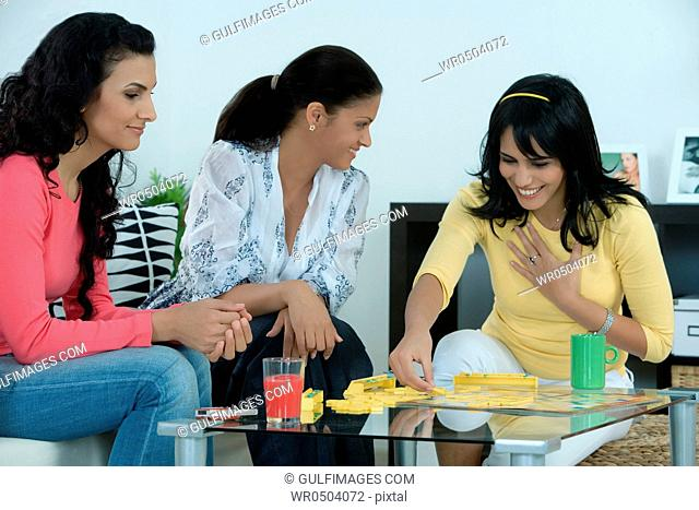 Three women playing scrabble in the living room