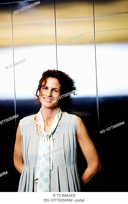 Business woman in elevator, smiling