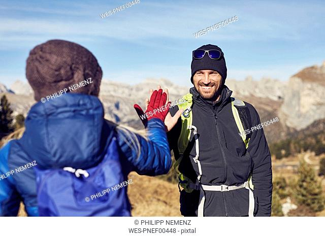 Smiling man and woman hiking in the mountains high fiving