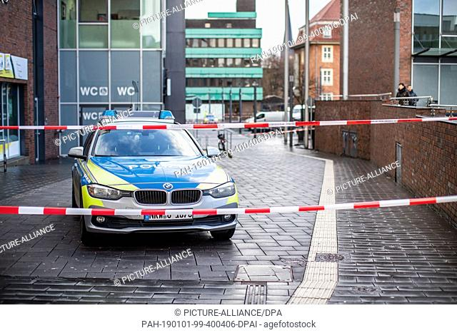 01 January 2019, North Rhine-Westphalia, Bottrop: A police car is standing behind barrier tape on Berliner Platz. On New Year's Eve