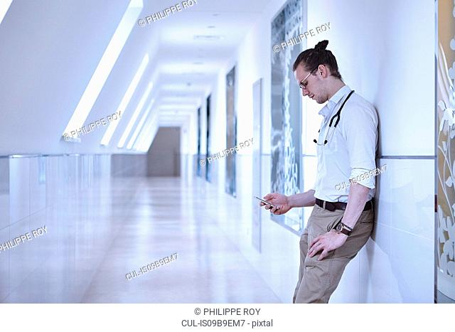Doctor in hospital corridor leaning against wall using smartphone