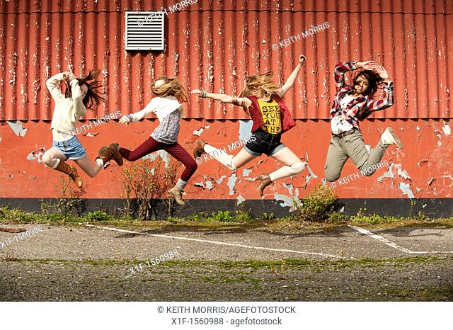 A group of 13 year old teenage girls leaping in the air UK