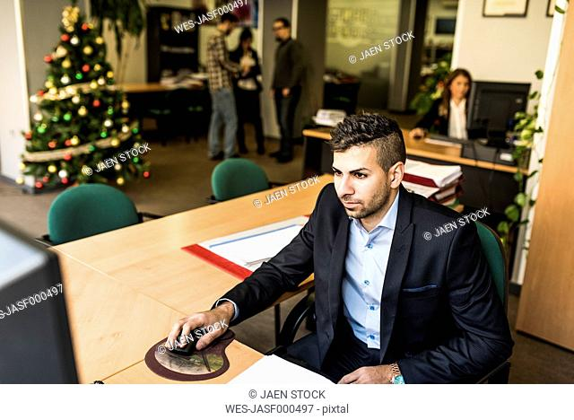 Man working at desk in office with Christmas tree in background