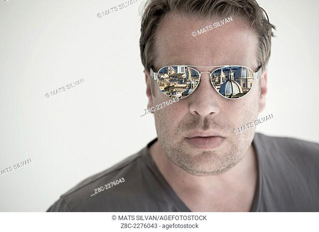 Man with sunglasses and cityscape reflected in the sunglasses in Rome, Italy