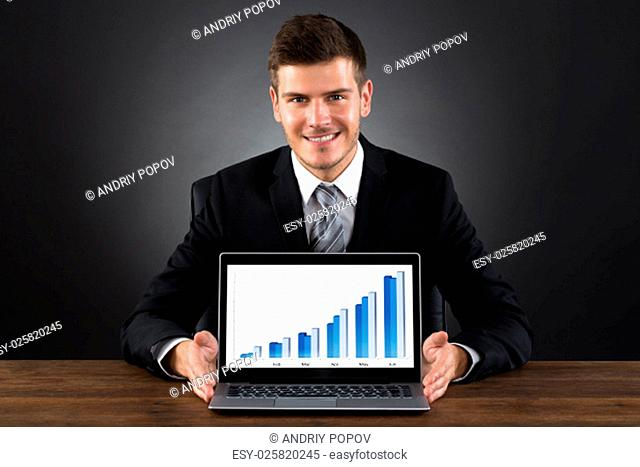 Young Happy Businessman Showing Graph On Laptop At Wooden Desk