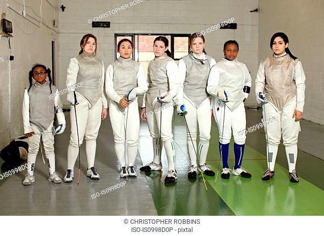 Portrait of female fencers standing together in a row