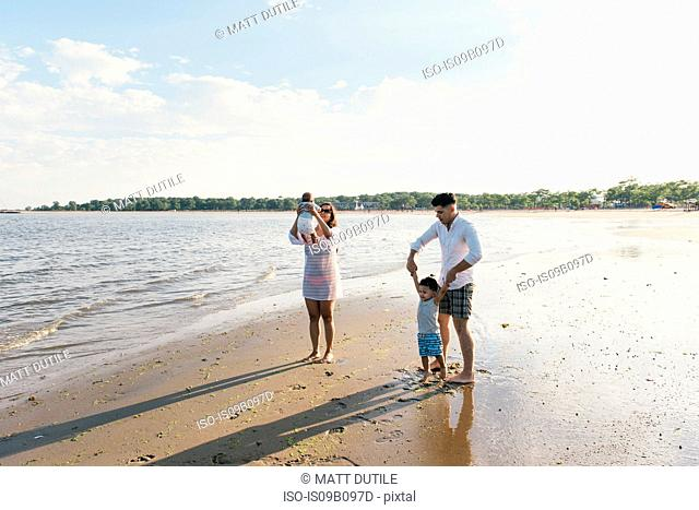 Parents playing with toddler son and baby boy on beach at Pelham Bay Park, Bronx, New York, USA