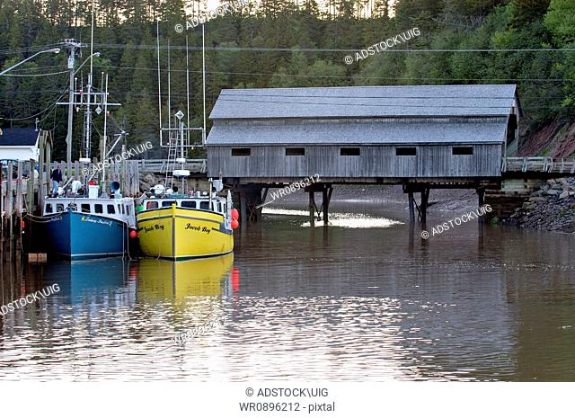 Salt water fishing boats moored for the night in an east coast safe harbour in Saint Martins New Brunswick, Canada