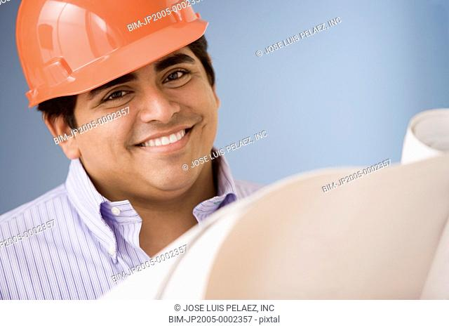 Construction worker wearing a hard hat while looking at blueprints