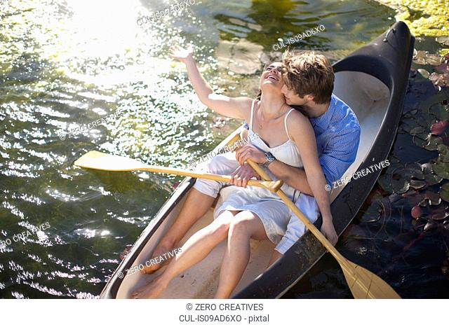 Young couple hugging in rowing boat