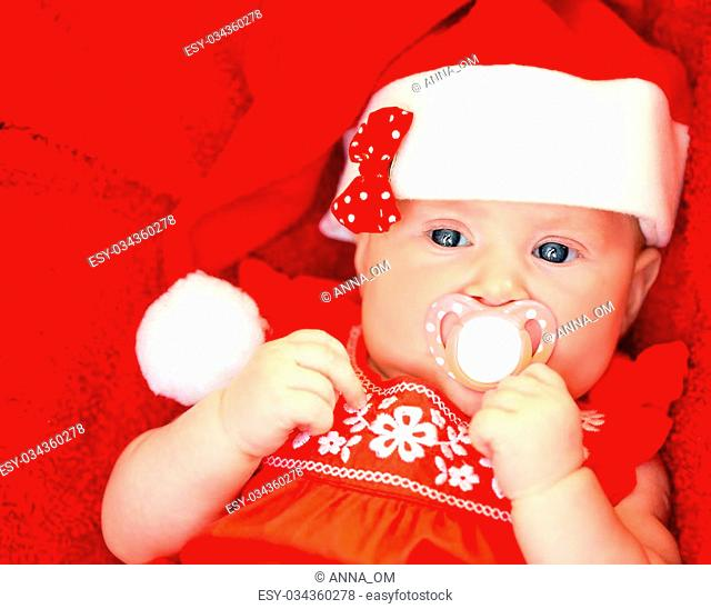 Closeup portrait of adorable newborn girl with pacifier in mouth wearing red festive Santa hat, New Year celebration, Christmas holiday, happy childhood concept