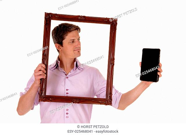 A young man holding up a picture frame, looking trough on his tablet,.isolated for white background.