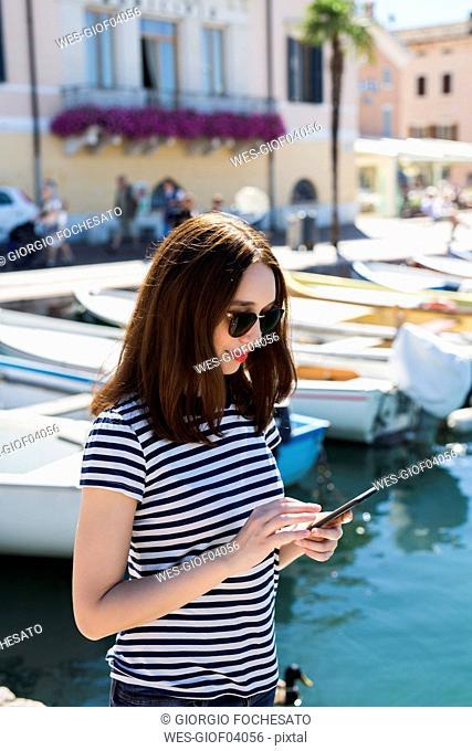 Italy, Bardolino, Lake Garda, young woman using cell phone