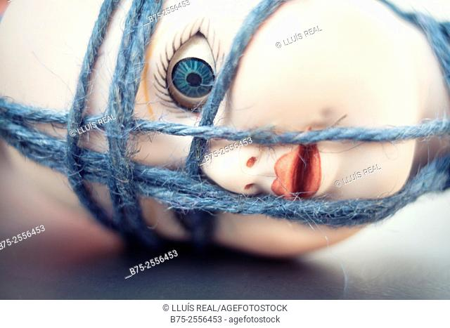 Head of antique porcelain doll tied with a blue rope