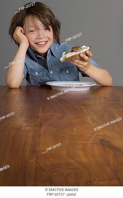 Boy eating open-faced sandwich