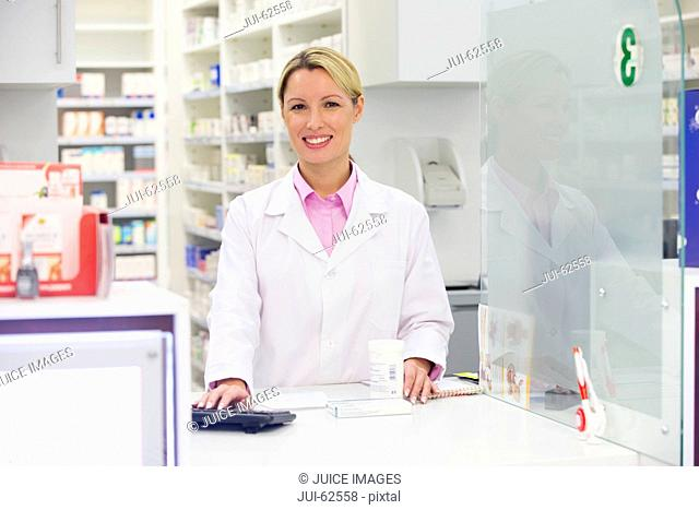 Pharmacist smiling at pharmacy counter
