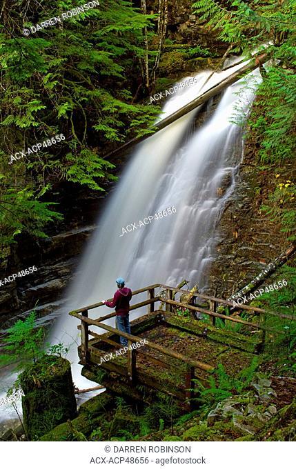 Hiker enjoys the views of David Lam Falls from the boardwalk along the Blackwater Creek Trail, near Powell River on British Columbia's Sunshine Coast, Canada