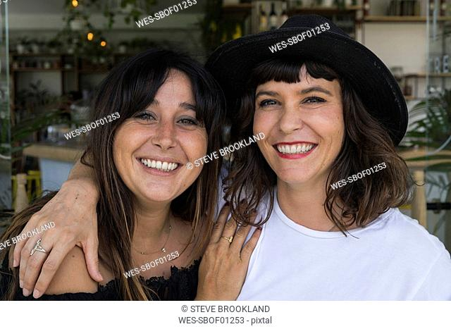 Portrait of two female friends hugging each other in a cafe