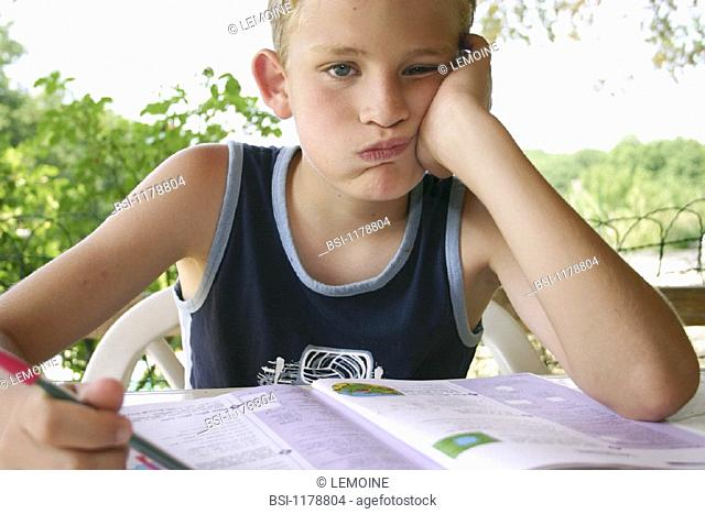 CHILD DOING HOMEWORK OUTDOORS<BR>Model.<BR>11-year-old boy