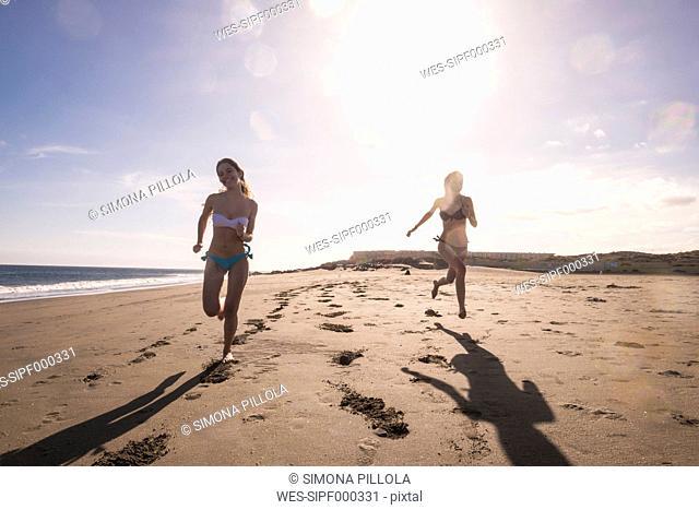 Spain, Tenerife, two female friends running on the beach